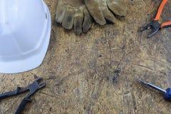 Herramientas de funcionamiento de un constructor en un emplazamiento de la obra, mintiendo en una tabla de escritorio de madera Foto de archivo