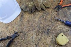 Herramientas de funcionamiento de un constructor en un emplazamiento de la obra, mintiendo en una tabla de escritorio de madera Fotografía de archivo libre de regalías