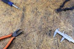 Herramientas de funcionamiento de un constructor en un emplazamiento de la obra, mintiendo en una tabla de escritorio de madera Imágenes de archivo libres de regalías