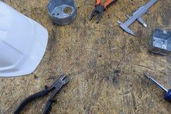 Herramientas de funcionamiento de un constructor en un emplazamiento de la obra, mintiendo en una tabla de escritorio de madera Imagen de archivo