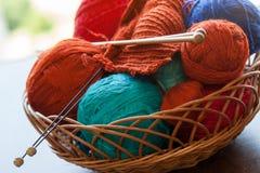 Herramientas de Knitwork y bolas del hilo en una cesta Fotografía de archivo