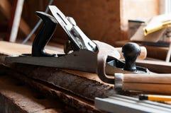 Herramientas de la carpintería en los tableros de madera, foco en el avión fotos de archivo libres de regalías
