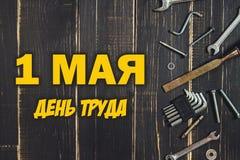 Herramientas de la carpintería en una tabla de madera oscura Lugar para el texto Texto en ruso: 1 de mayo, Día del Trabajo Imágenes de archivo libres de regalías