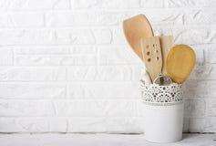 Herramientas de la cocina, tabla de cortar verde oliva en un estante de la cocina contra una pared de ladrillo blanca Foco select Imagen de archivo