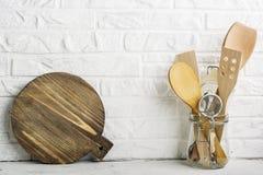 Herramientas de la cocina, tabla de cortar verde oliva en un estante de la cocina contra una pared de ladrillo blanca Foco select Fotografía de archivo libre de regalías