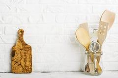Herramientas de la cocina, tabla de cortar verde oliva en un estante de la cocina contra una pared de ladrillo blanca Foco select Imágenes de archivo libres de regalías