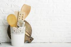 Herramientas de la cocina, tabla de cortar verde oliva en un estante de la cocina contra una pared de ladrillo blanca Foco select Foto de archivo libre de regalías