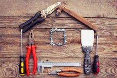 Herramientas de la construcción bajo la forma de casa en fondo de madera Imágenes de archivo libres de regalías