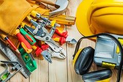 Herramientas de la construcción del casco en correa y caja de herramientas de la herramienta con los auriculares en los tableros  foto de archivo libre de regalías
