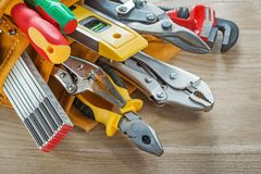 Herramientas de la construcción en toolbelt en el tablero de madera Imagen de archivo libre de regalías