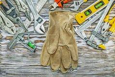 Herramientas de la construcción de los guantes de la seguridad en el tablero de madera Foto de archivo libre de regalías