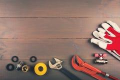 Herramientas de la fontanería en la tabla de madera con el copyspace Foto de archivo libre de regalías