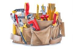 Herramientas de la mano de la construcción en la correa de cuero marrón de la herramienta aislada en blanco foto de archivo libre de regalías