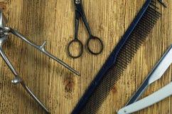 Herramientas de la peluquería del vintage en un de madera áspero Foto de archivo