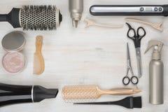 Herramientas de la peluquería en fondo de madera con el copyspace en el centro Foto de archivo libre de regalías