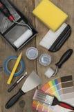 Herramientas de la pintura, latas de la pintura, y muestras de la pintura en Backgro de madera fotografía de archivo libre de regalías