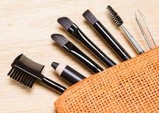 Herramientas de la preparación de la ceja en bolso cosmético anaranjado Imagenes de archivo