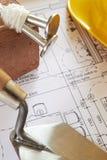 Herramientas de los constructores dispuestas en planes de la casa Imagen de archivo libre de regalías