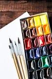 Herramientas del arte - pinturas y cepillos de la acuarela con el Libro Blanco en blanco Imagen de archivo