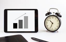 Herramientas del asunto tableta con un gráfico del crecimiento Relojes Foto de archivo libre de regalías