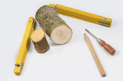 Herramientas del carpintero con el tocón de madera en el fondo blanco Fotografía de archivo libre de regalías