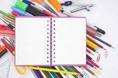 Herramientas del cuaderno y de la escuela o de la oficina en el fondo blanco Fotos de archivo