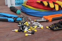 Herramientas del electricista con el alambre rojo y azul presentado en una superficie de madera del color oscuro Visi?n superior imagen de archivo libre de regalías