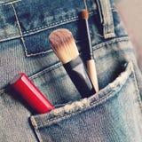 Herramientas del maquillaje del primer en bolsillo trasero de los vaqueros Imágenes de archivo libres de regalías