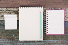Herramientas del papel y de la escuela o de la oficina del cuaderno en la tabla de madera del vintage Imágenes de archivo libres de regalías