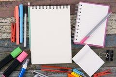 Herramientas del papel y de la escuela o de la oficina del cuaderno en la tabla de madera del vintage Fotos de archivo libres de regalías