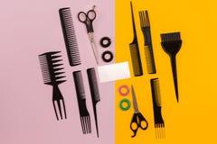 Herramientas del peluquero en fondo rosado y amarillo con el espacio de la copia, visión superior, endecha plana Fotografía de archivo libre de regalías
