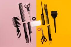 Herramientas del peluquero en fondo rosado y amarillo con el espacio de la copia, visión superior, endecha plana Imagenes de archivo