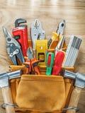 Herramientas en el toolbelt de cuero en la opinión superior del tablero de madera Foto de archivo