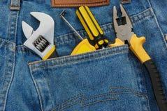 Herramientas en un bolsillo azul de la mezclilla Imágenes de archivo libres de regalías