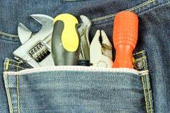 Herramientas en un bolsillo azul de la mezclilla Fotos de archivo libres de regalías