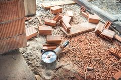 Herramientas industriales del emplazamiento de la obra, amoladora de ángulo usada para cortar ladrillos en la renovación del edif Imagen de archivo