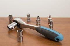 Herramientas, llave de trinquete azul y accesorios en una tabla de madera Imagenes de archivo