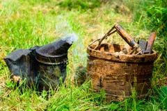 Herramientas para el apicultor en la hierba verde, humo Imagenes de archivo