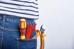 Herramientas para el electricista en el bolsillo trasero de tejanos llevados por una mujer Lazos, cortadores y destornillador de  Foto de archivo libre de regalías