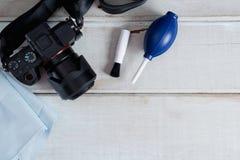 Herramientas para limpiar la cámara con la cámara del dslr en el fondo de madera blanco Foto de archivo libre de regalías