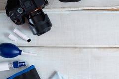 Herramientas para limpiar la cámara con la cámara del dslr en el fondo de madera blanco Fotografía de archivo libre de regalías