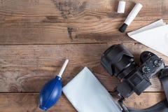 Herramientas para limpiar la cámara con la cámara del dslr en fondo de madera Fotos de archivo