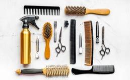Herramientas para los hairdress en barbería en la opinión superior del fondo blanco Imagenes de archivo