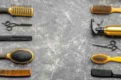Herramientas para los hairdress en barbería en maqueta gris de la opinión superior del fondo Foto de archivo