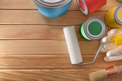 Herramientas para pintar de casas en la sobremesa de madera del listón imagen de archivo