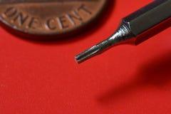 Herramientas, pequeño destornillador de Philips en fondo rojo Imagen de archivo