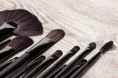 Herramientas profesionales del artista de maquillaje en superficie de madera lamentable Imagenes de archivo