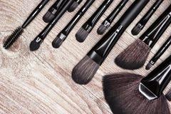 Herramientas profesionales del artista de maquillaje en superficie de madera lamentable Imagen de archivo libre de regalías