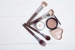 Herramientas profesionales del maquillaje en el fondo de madera blanco Imágenes de archivo libres de regalías