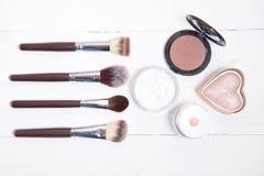 Herramientas profesionales del maquillaje en el fondo de madera blanco Fotos de archivo libres de regalías